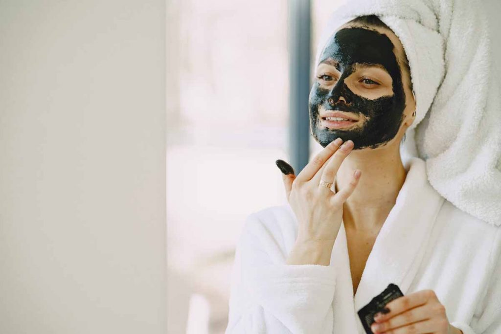 Woman rubbing clay mask on face - Frankincense & clay facial mask